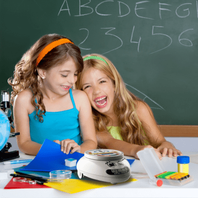 Girls and the educational robot Roamer laugh.